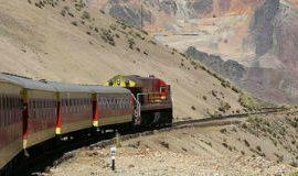 A Peruvian train chugging along a mountainside.