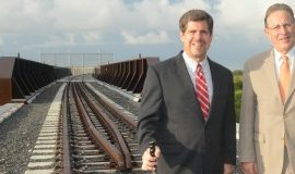 US Ambassador Anthony Wayne posing  for a photo beside the US-Mexico railroad.